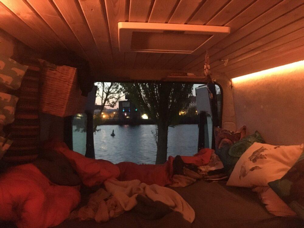 Gemütliches Licht im Camper Van mit geöffneten Hecktüren und Blick auf's Wasser