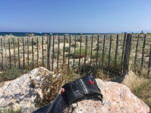 Solardusche als praktischer Artikel im VanLife beim Erhitzen auf einem Stein am Strand