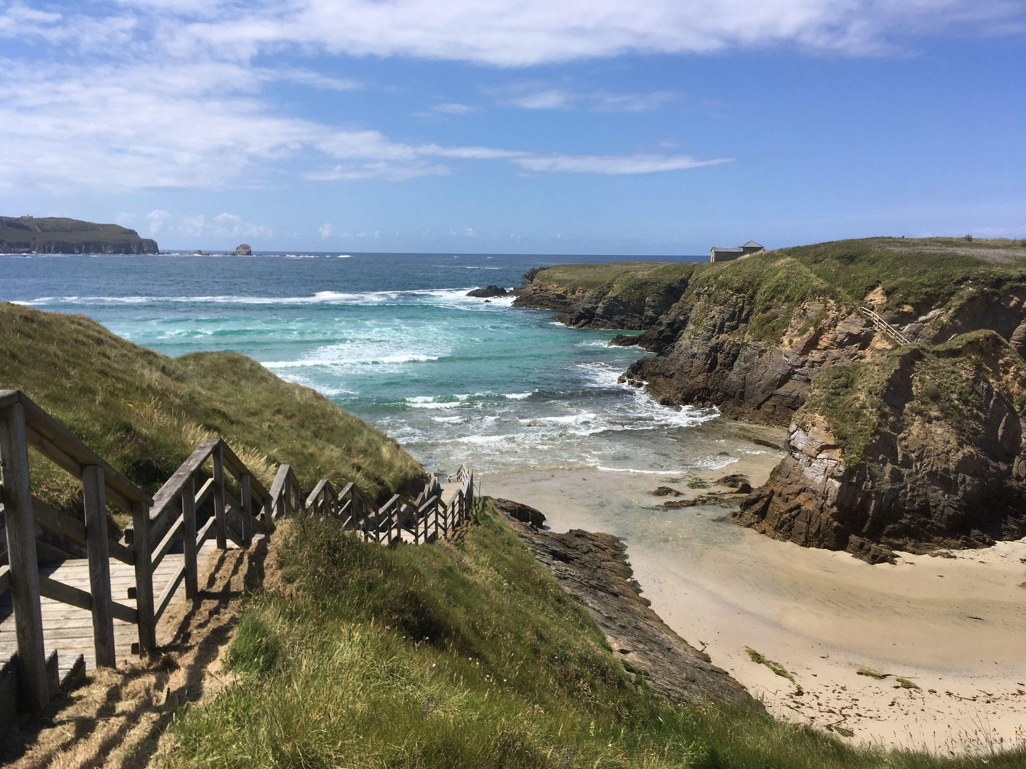 Treppe zum Strand mit Blick auf abgelegene Insel mit Kirche bei Sonnenschein
