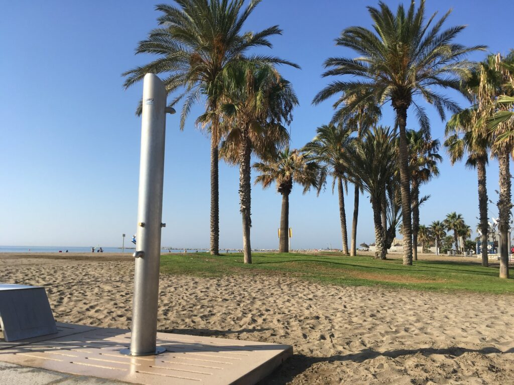 Stranddusche am Meer vor Palmen als Hilfsmittel zur Hygiene im Camper Van