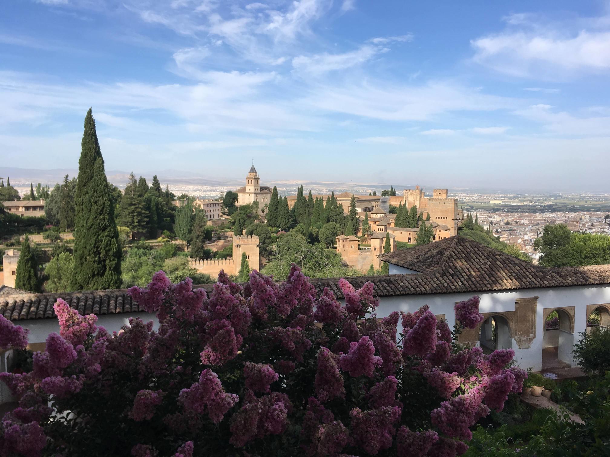 Blick auf die Burganlage Alhambra vom Generalife Palast aus mit Flieder und Zypresse im Vordergrund