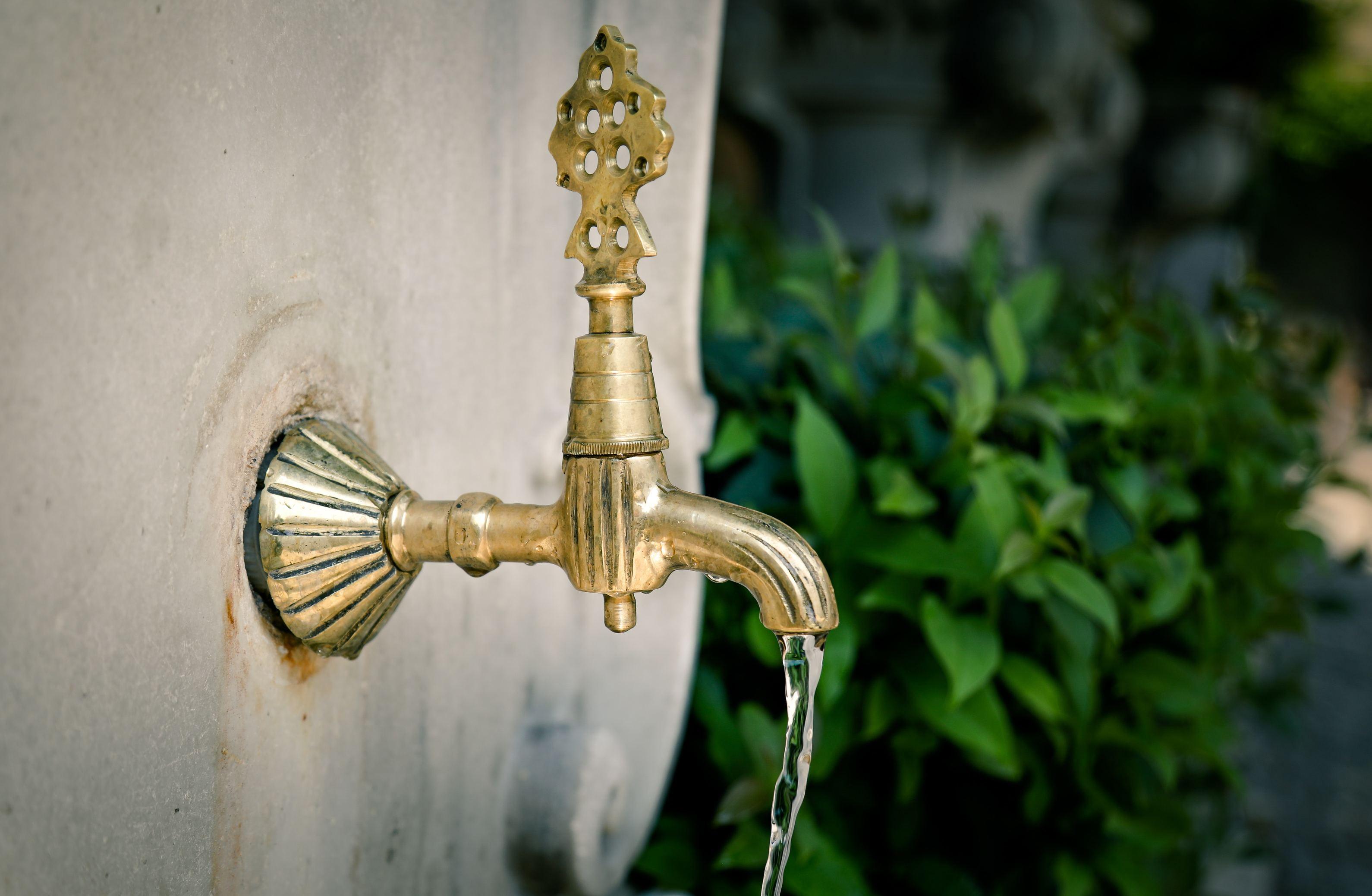 Goldener Wasserhahn am Brunnen mit fließend Wasser