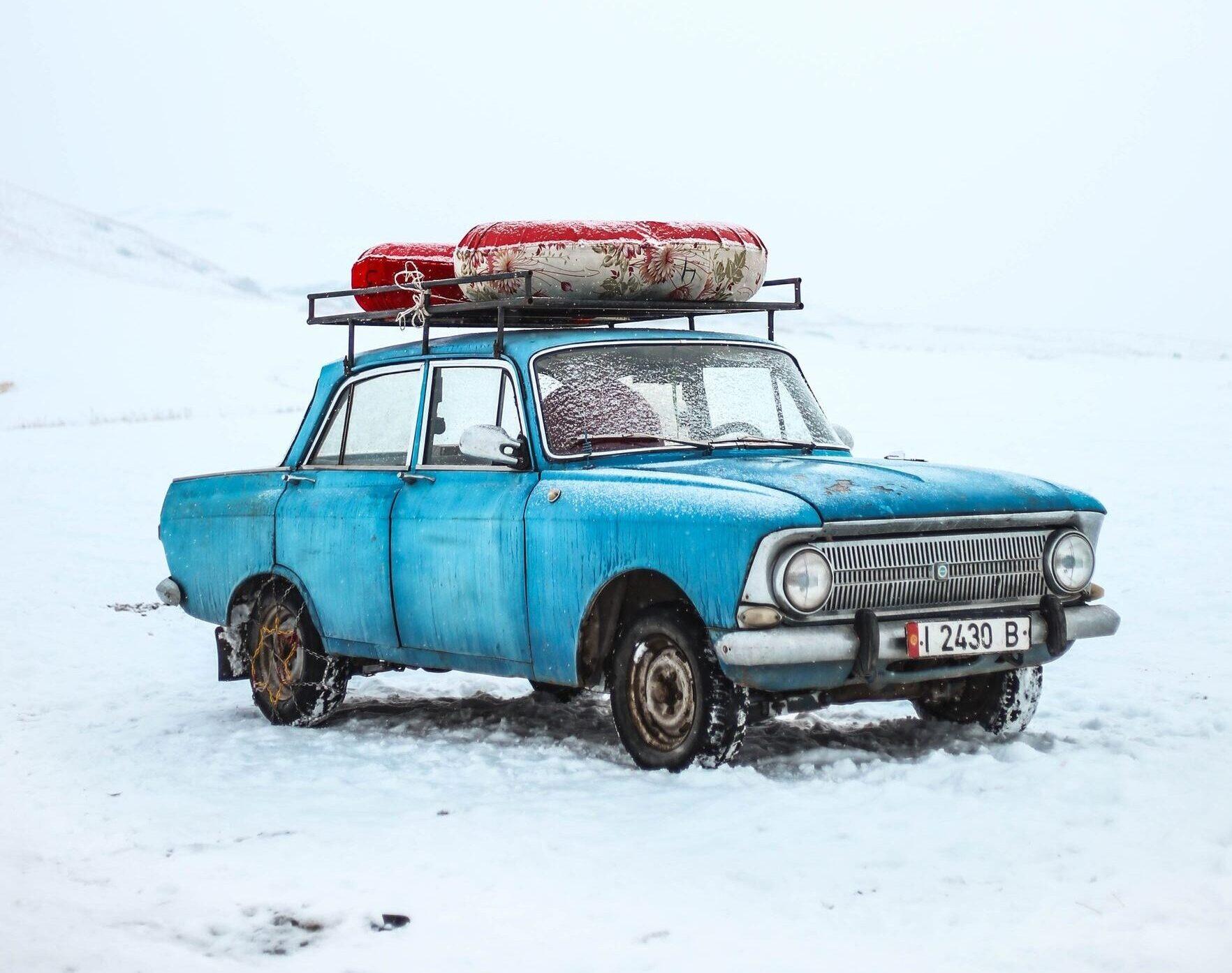 Blauer Van in schneebedeckter Landschaft